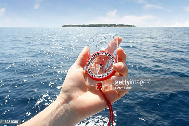 hand holding compass, island in background