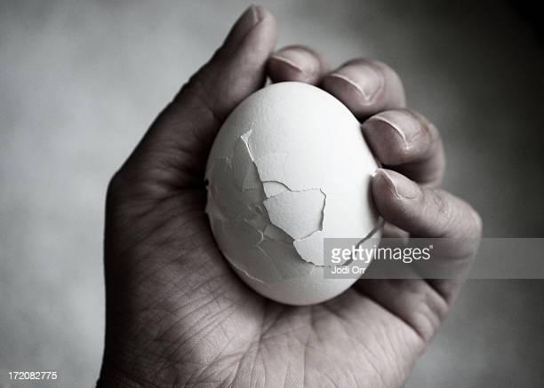 Hand holding cracked egg