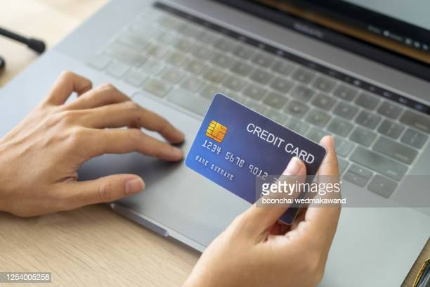 hand holding credit card and using laptop. businesswoman or entrepreneur working from home. - fraud stock pictures, royalty-free photos & images