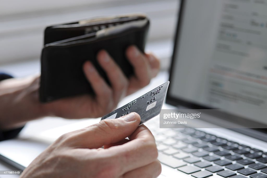 hand holding credit card and wallet by laptop : Stock Photo