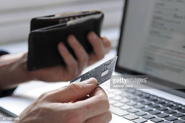 hand holding credit card and wallet by laptop - home shopping stock pictures, royalty-free photos & images