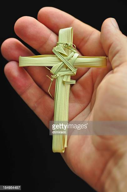 hand holding cross made out of palm fronds - palm sunday stock pictures, royalty-free photos & images