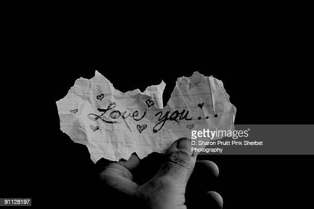 hand holding crumpled love letter - love letter stock photos and pictures