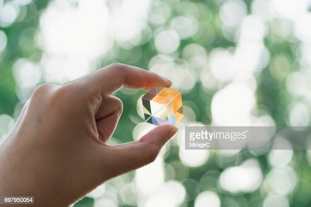 hand holding cube prism against green trees bokeh - völlig lichtdurchlässig stock-fotos und bilder