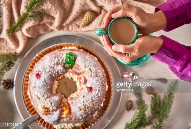 hand holding cup of coffee above spanish christmas cake - roscon de reyes stock pictures, royalty-free photos & images
