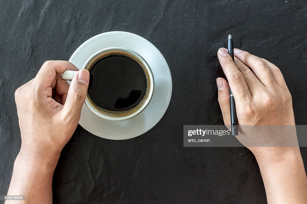 Hand holding cup of coffee and pen on black background : Stock Photo