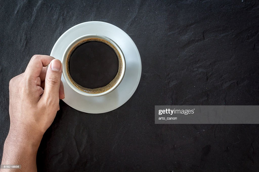 Hand holding cup of coffee  on black background : Stockfoto