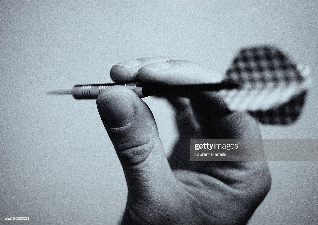 Hand holding dart, close-up, b&w. : Stockfoto