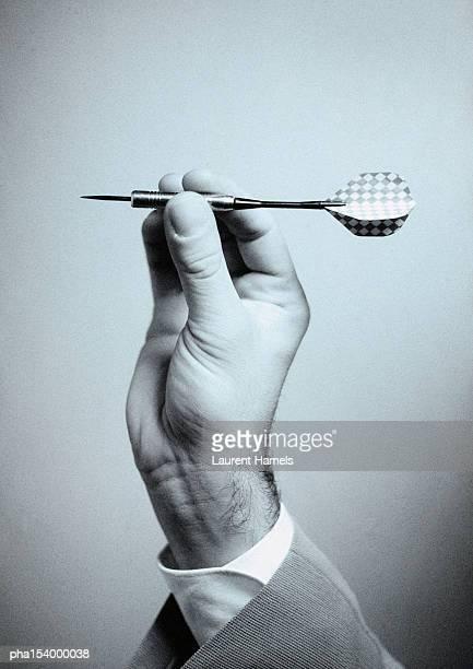 Hand holding dart, close-up, b&w.