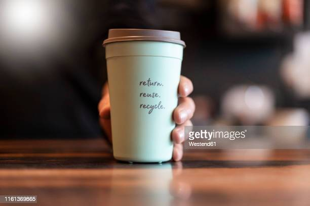 hand holding deposit cup for coffee to go, close-up - western script stock pictures, royalty-free photos & images