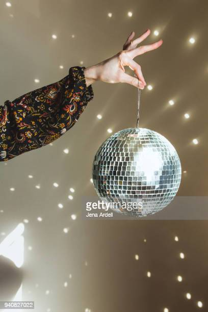 hand holding disco ball retro 1970s - disco ball stock photos and pictures
