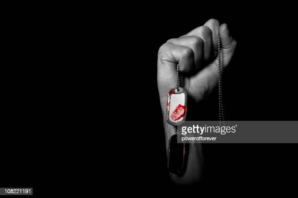 hand holding dog tags covered with blood - military dog tags stock pictures, royalty-free photos & images