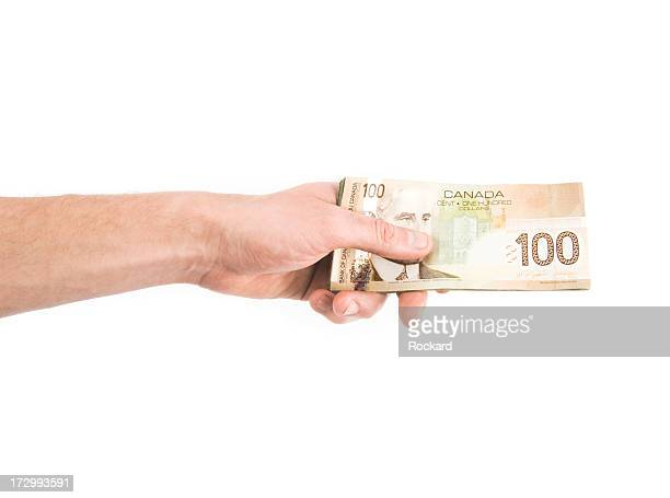hand holding dollar bills against white background - canadian one hundred dollar bill stock pictures, royalty-free photos & images