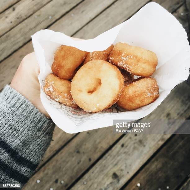 hand holding donuts - fishermans wharf stock pictures, royalty-free photos & images