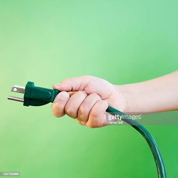 hand holding electrical cord - plugging in stock pictures, royalty-free photos & images