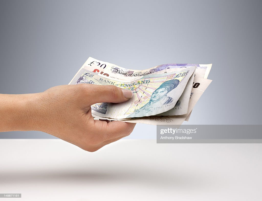 Hand holding English currency : Stock Photo
