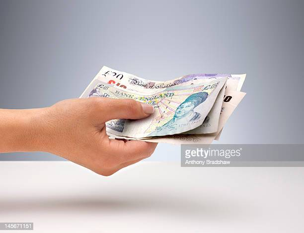 hand holding english currency - giving stock photos and pictures