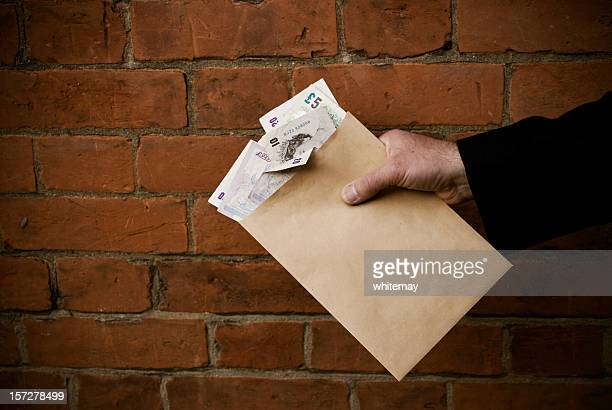 hand holding envelope and bank notes - passing giving stock photos and pictures