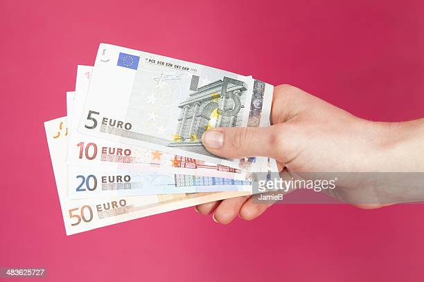 hand holding euro bank notes - five euro banknote stock photos and pictures