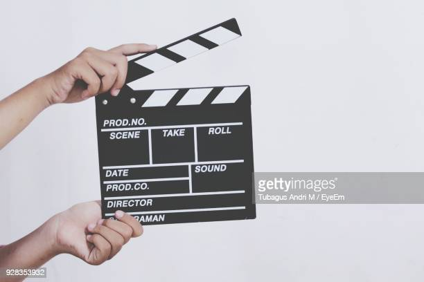hand holding film slate over white background - industrie du cinéma photos et images de collection