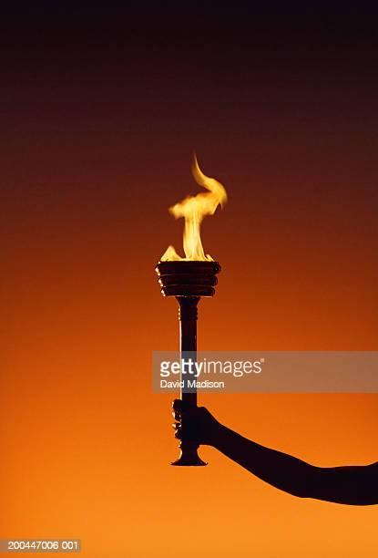 hand holding flaming torch, close-up - 聖火トーチ ストックフォトと画像