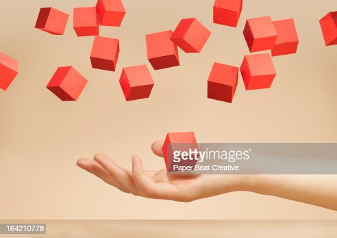 hand holding floating paper boxes in the studio