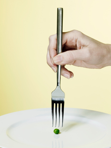 Hand holding fork above a pea - gettyimageskorea