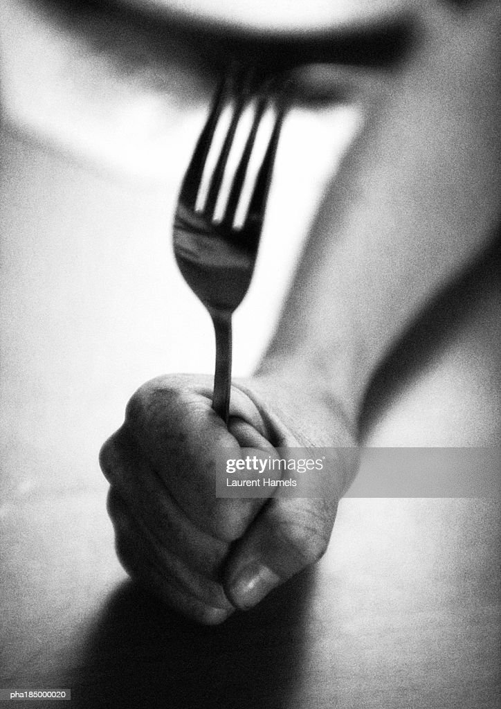 Hand holding fork, close-up, b&w : Stockfoto