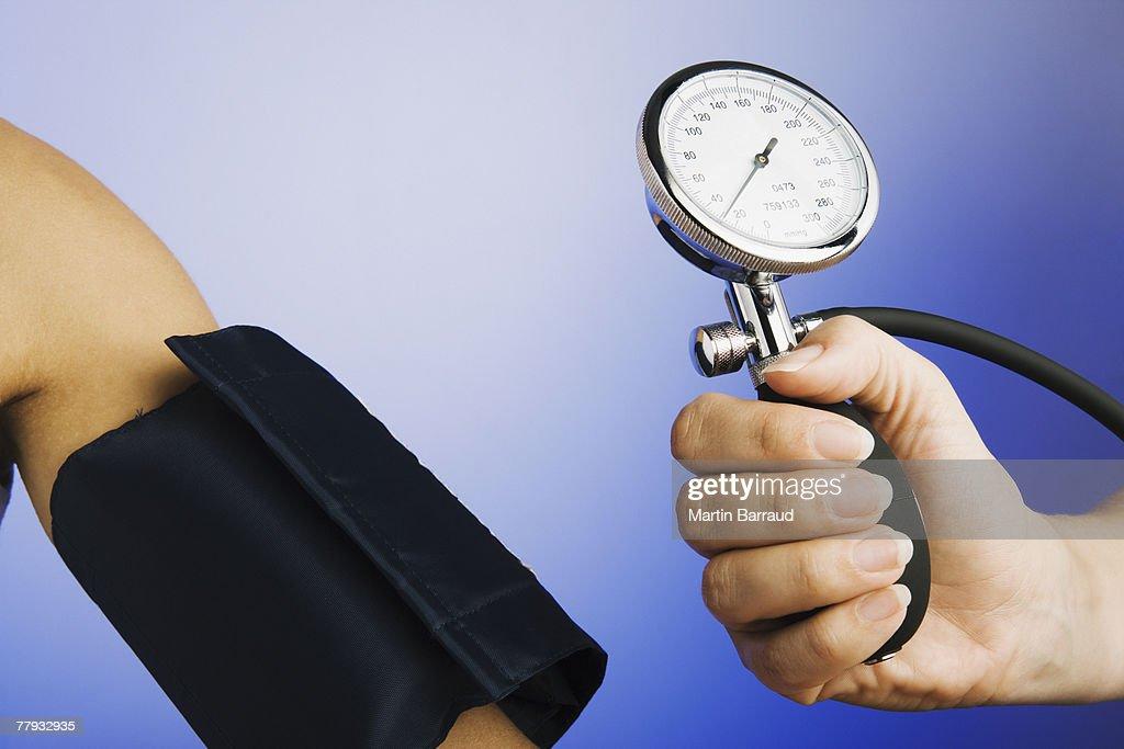 Mão a segurar na pressão arterial de calibre dispositivo perto braço do doente. : Foto de stock