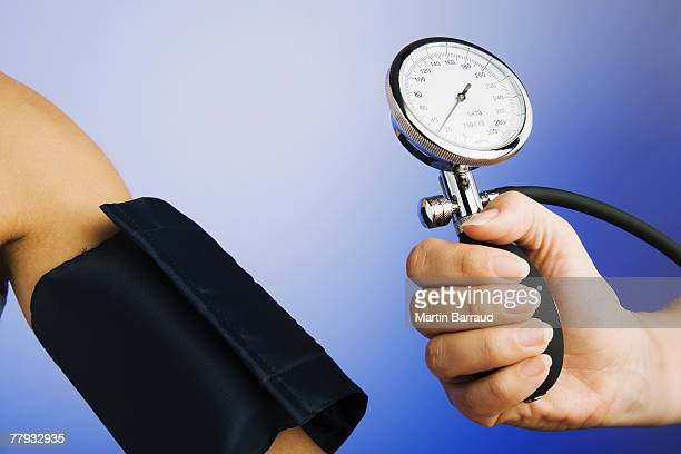 Hand holding gage for blood pressure device near patient's arm