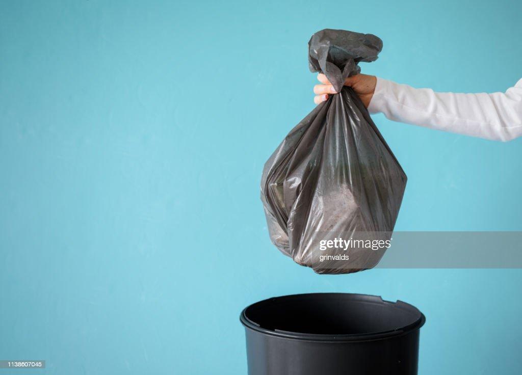 ビニール袋にごみを持っている手 : ストックフォト
