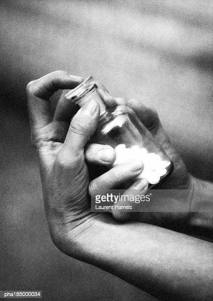 hand holding glass  medicine bottle, close-up, b&w - suicidio pastillas fotografías e imágenes de stock