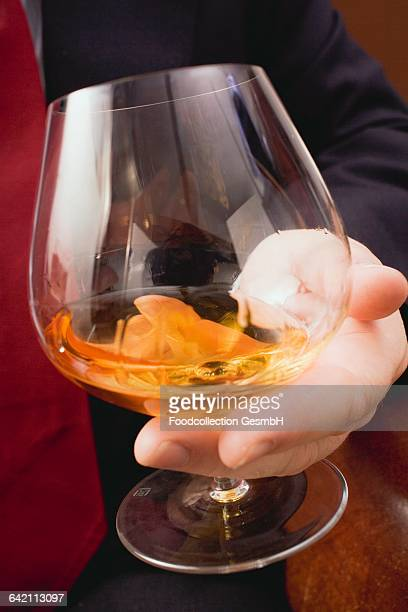 Hand holding glass of cognac