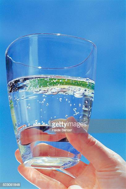 hand holding glass of sparkling water with lime slice - carbonated water stock pictures, royalty-free photos & images