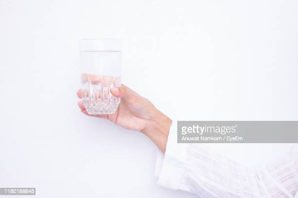 hand holding glass of water against white background - ガラス ストックフォトと画像