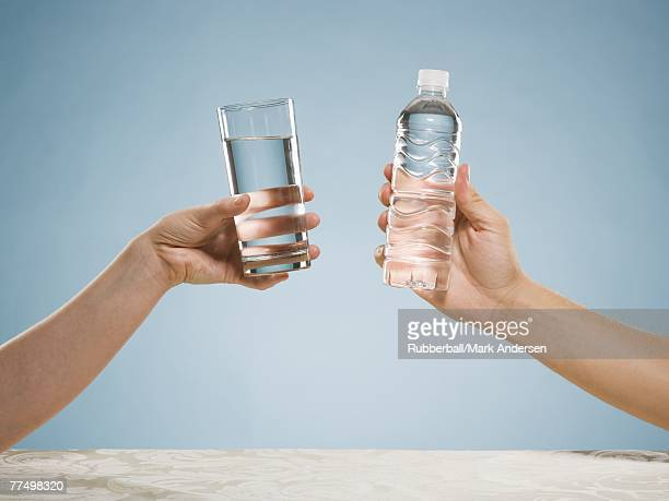 Hand holding glass of water and hand holding bottled water