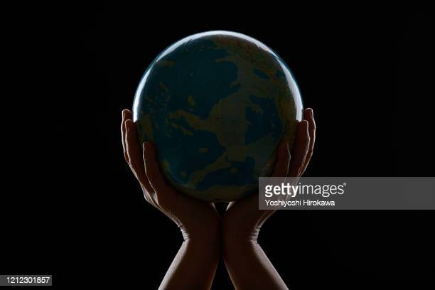 hand holding globe - world politics stock pictures, royalty-free photos & images