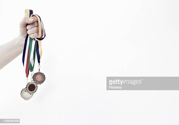 Hand holding gold, silver and bronze medals