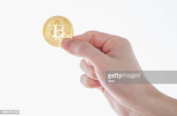 白い背景の黄金 bitcoin コインを持っている手