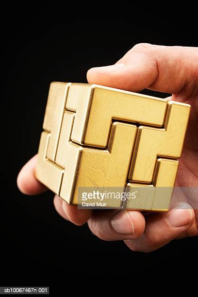 Hand holding golden puzzle cube, close-up