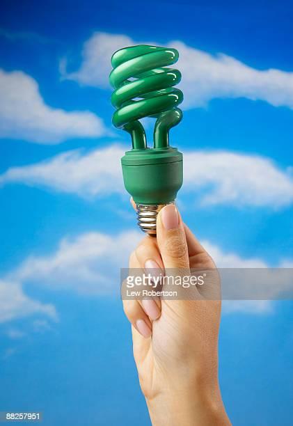 Hand Holding Green Compact Flourescent Light Bulb