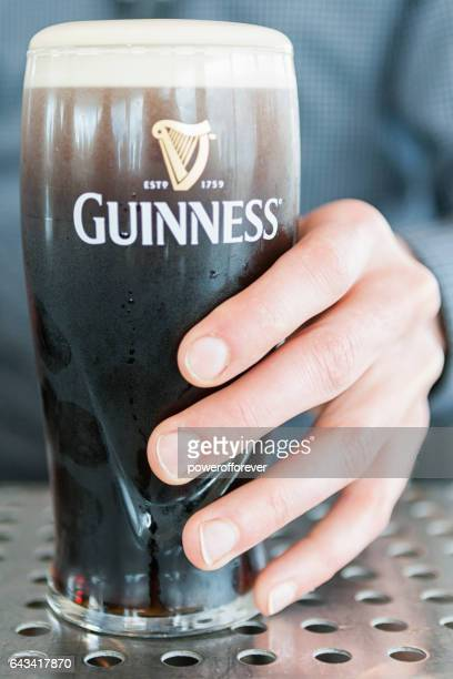 hand holding guinness beer - guinness stock photos and pictures