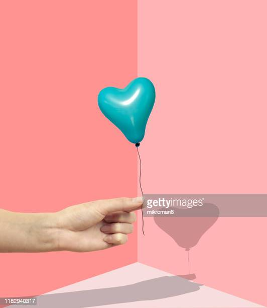 hand holding heart shaped balloon with two fingers - valentines day stock pictures, royalty-free photos & images