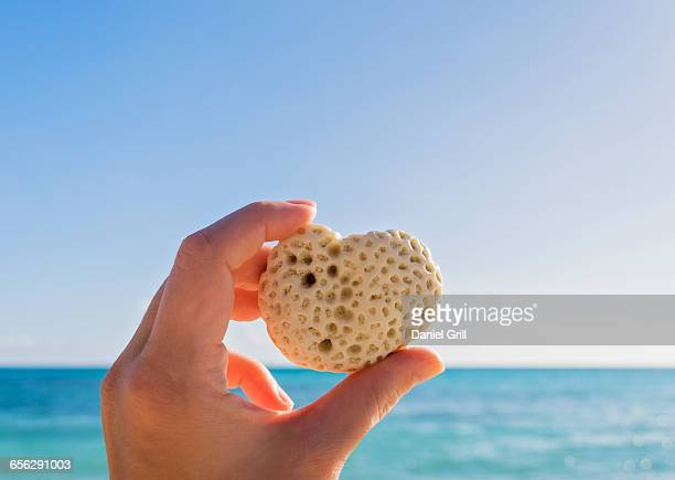 Hand holding heart-shaped shell against sea and blue sky