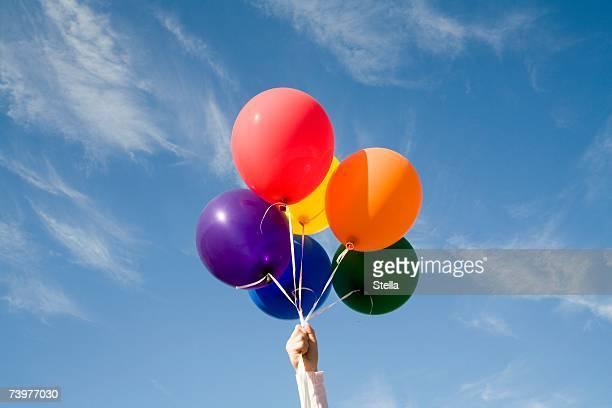 Hand holding helium balloons