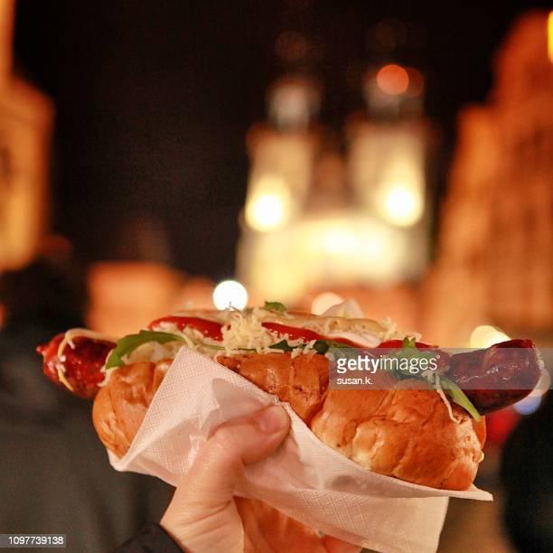 hand holding hotdog at christmas market. - notre dame de tyn photos et images de collection