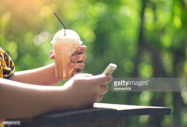hand holding ice coffee and smartphone with green background