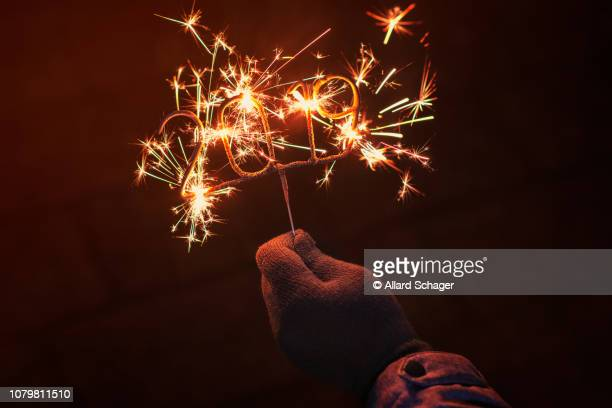 hand holding igniting 2019 sparkler - 2019 stock pictures, royalty-free photos & images