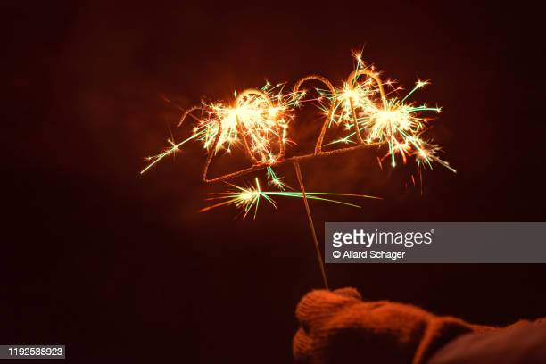hand holding igniting 2020 sparkler - 2020 stock pictures, royalty-free photos & images