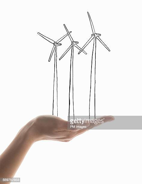 Hand holding illustrated wind mills